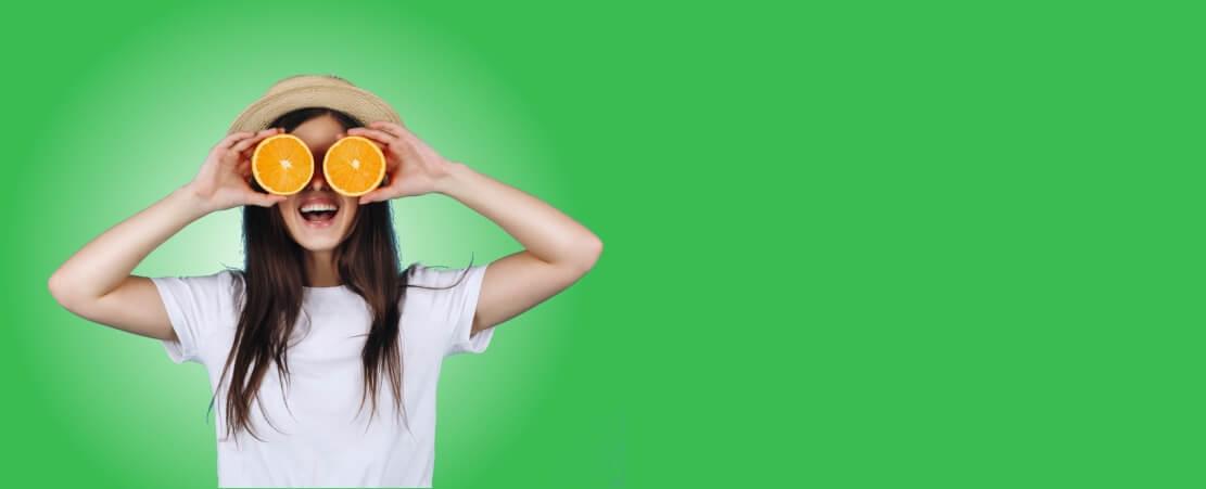 chica con naranjas fondo verde